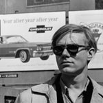 Andy in front of a Chevy billboard, spring 1965